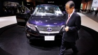 A visitor walks about Toyota Motor Corps.'s hybrid Lexus RX450h on display at the Tokyo Motor Show