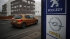 A Peugeot car drives past the logos of French car maker Peugeot and German car maker Opel