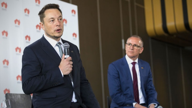 South Australian Premier Jay Weatherill (R) listens to Tesla Chief Executive Officer Elon Musk speak