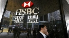 A man walks past a logo of HSBC outside a branch at the financial Central district in Hong Kong