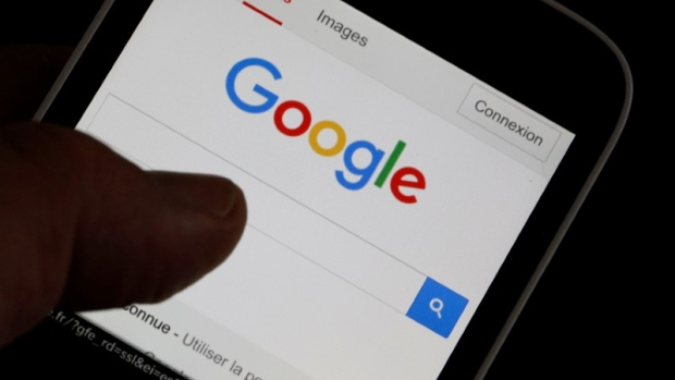 A man holds his smartphone which displays the Google home page in this picture illustration