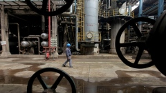 A worker walks past oil pipes at a refinery in Wuhan, Hubei province March 23, 2012.