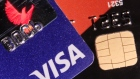 A VISA credit card is pictured next to a computer chip on a bank card in this photo illustration