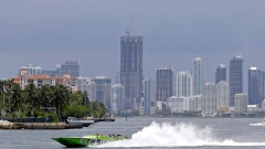 A boat speeds out to sea across the downtown Miami skyline