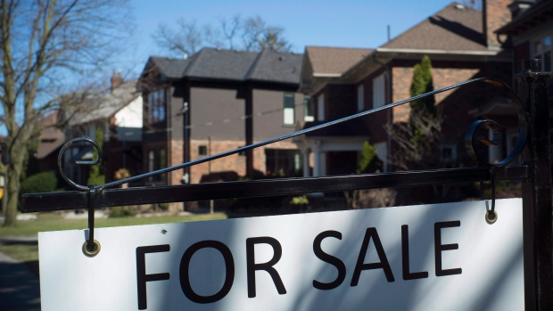 "A ""For Sale"" sign is shown in front of west-end Toronto homes"