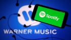 Spotify's logo is seen on a smartphone in front a Warner Music logo in this picture illustration