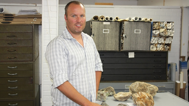 Margaux President, Tyler Rice, inspecting rock samples at the company's Salmo office.