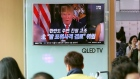 People watch a TV screen showing a local news program with an image of U.S. President Donald Trump