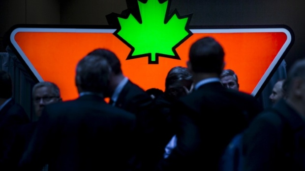 People stand in front of a large Canadian Tire Corp logo during their annual general meeting for shareholders in Toronto