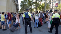 Police officers tell members of the public to leave the scene in a street in Barcelona