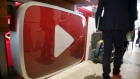 A man walks past a YouTube logo at the YouTube Space LA in Playa Del Rey, Los Angeles