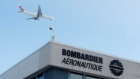 A plane flies over a Bombardier plant in Montreal, Quebec