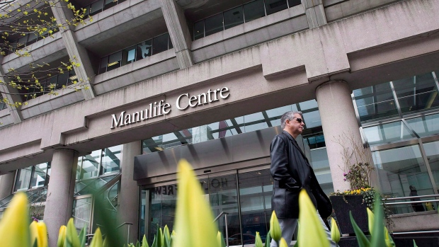 A man walks by the Manulife Centre in Toronto