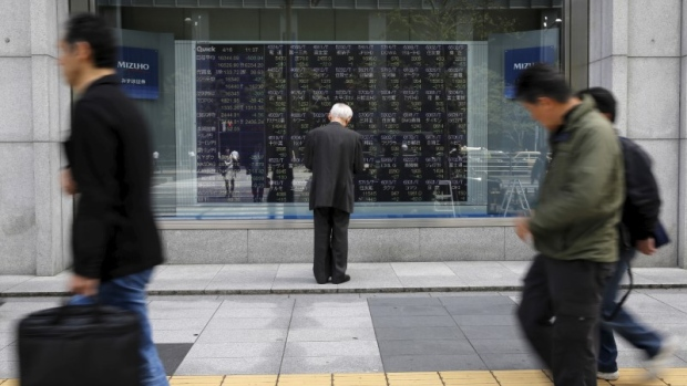 A man looks at a stock quotation board outside a brokerage in Tokyo, Japan, April 18, 2016.