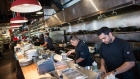 Line cooks Ishaan Kohli, right, and Abrahan Ruiz, second right, work in the kitchen at Edible Canada