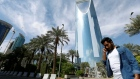 A man speaks on the phone as he walks past the Kingdom Centre Tower in Riyadh, Saudi Arabia