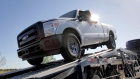 In this March 29, 2011 photo, new 2011 Ford F-250 trucks are delivered to a dealership in Glbert, AZ
