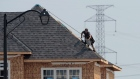 A construction worker shingles the roof of a new home in a development in Ottawa on July 6, 2015.
